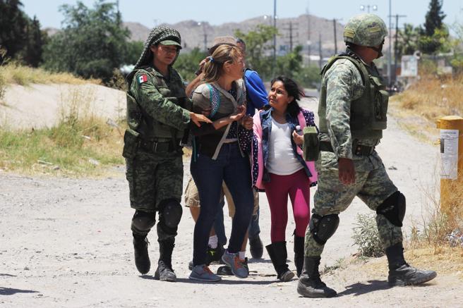 TOPSHOT - Miembros de la Guardia Nacional de México detienen a varias personas que intentaban cruzar  el río Bravo
