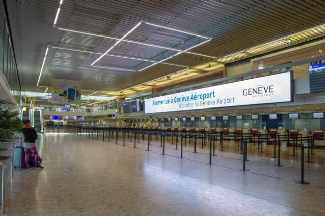 Una pasajera contempla los mostradores de facturación vacíos en el aeropuerto de Ginebra (Suiza), este martes,