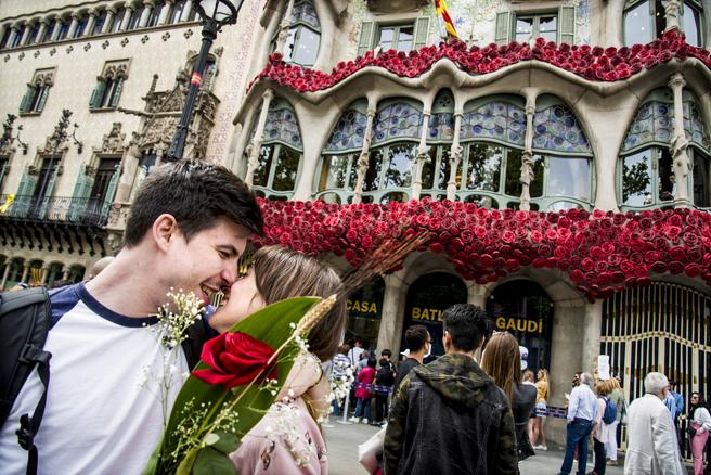 A couple celebrates a St. George's Day in front of Gaudí's Batló house
