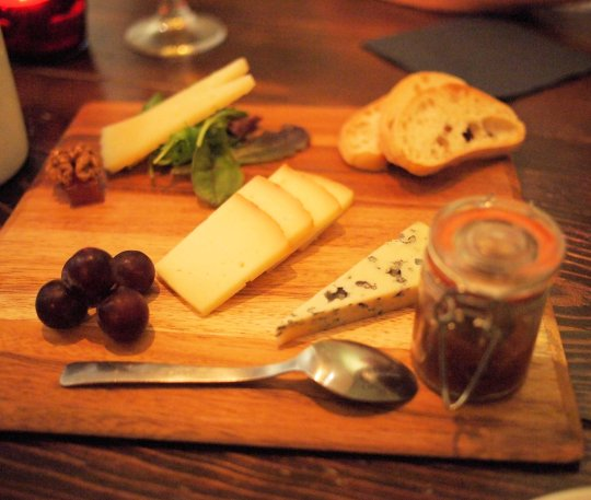 A mixed cheese board with fig jam, membrillo, walnuts, Manchego, Mahon and Valdeon cheeses