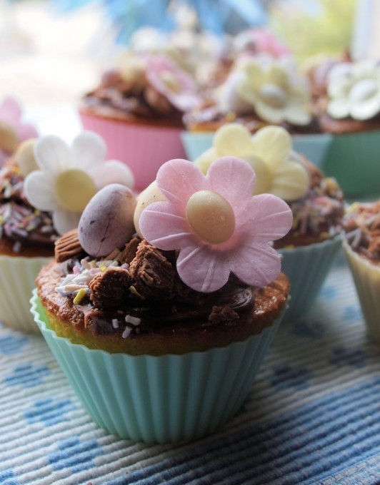 Delightful little vanilla Fairy cakes (cup cakes) that have a chocolate cream cheese topping with assorted edible decorations, perfect for the Easter Tea Time Table.