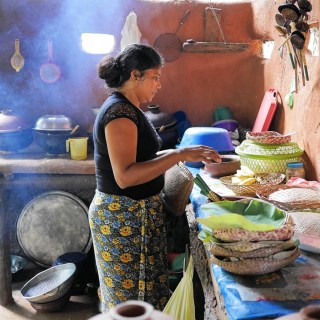 Woman cooking in traditional clay-pot jungle restaurant in Hiridunna VIllage