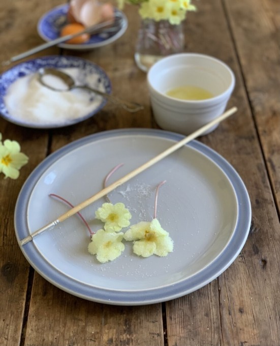 Place the dry fresh primroses on a breadboard, baking tray or flat surface. Beat the egg white to a light foam. Brush the flowers all over with beaten egg white, using a soft pastry brush or a paint brush.
