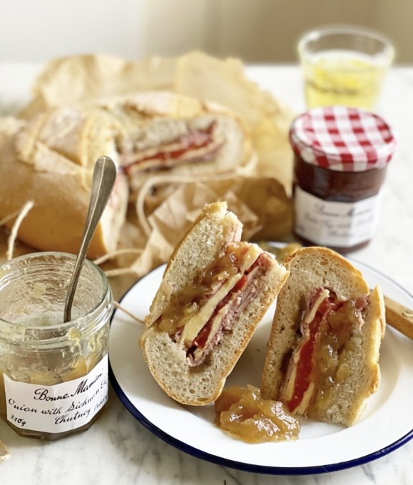Place some heavy weights on top of the sandwich and keep it in a cool place, such as the fridge, for up to 6 hours or until you need to serve it. Take the weights off the sandwich and unwrap the sandwich, then slice it to serve in wedges, or in thick slices.