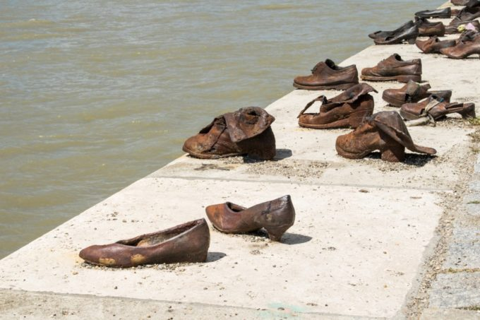 "The sculptor created sixty pairs of period-appropriate shoes out of iron. The shoes are attached to the stone embankment, and behind them lies a 40 meter long, 70 cm high stone bench. At three points are cast iron signs, with the following text in Hungarian, English, and Hebrew: ""To the memory of the victims shot into the Danube by Arrow Cross militiamen in 1944–45. Erected 16 April 2005.""[3]"