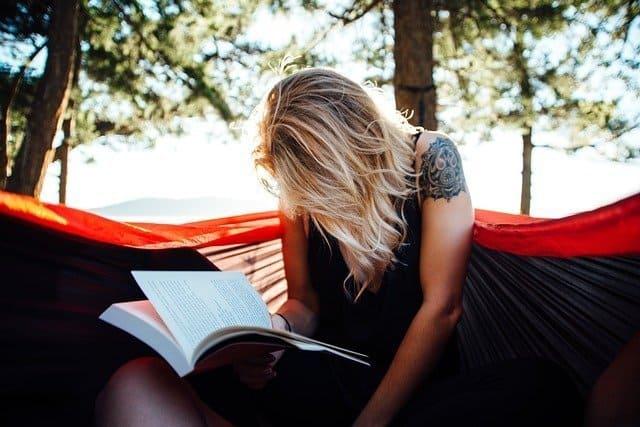 Una mujer leyendo un título de una lista de libros recomendados para empezar bien el año
