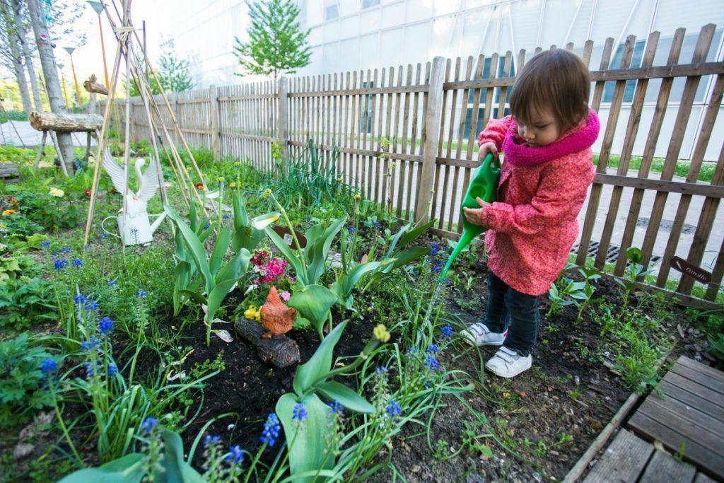 Les petits arrosent les fleurs dans le jardin partagé des assistantes maternelles