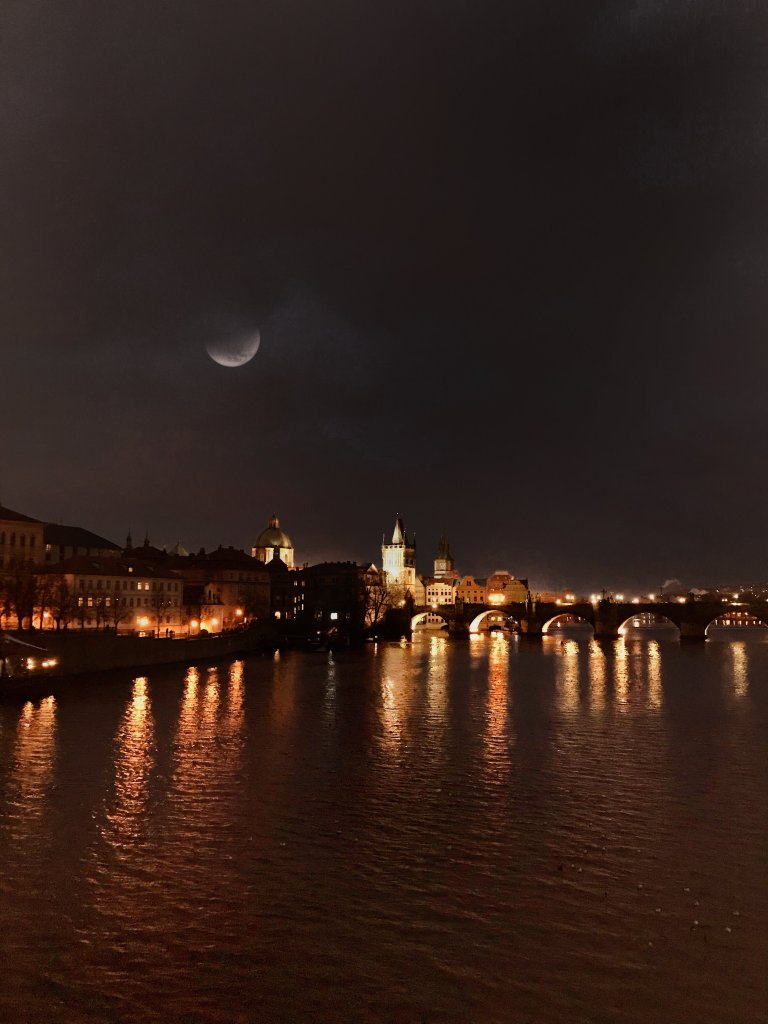 Vista di Praga in notturna dal ponte con la luna