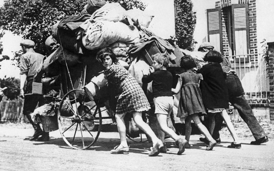 Une famille qui pousse la charette contenant les biens qu'ils ont pu sauver.