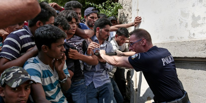 A Greek policeman tries to hold migrants behind a fence as they wait for a registration procedure outside a police station at southeastern island of Kos, Monday, Aug. 10, 2015.  Greece's coast guard rescued more than 1,400 migrants in nearly 60 search and rescue operations near several Greek islands in the eastern Aegean Sea over the past three days as the pace of new arrivals increase, authorities said Monday. (AP Photo/Yorgos Karahalis)