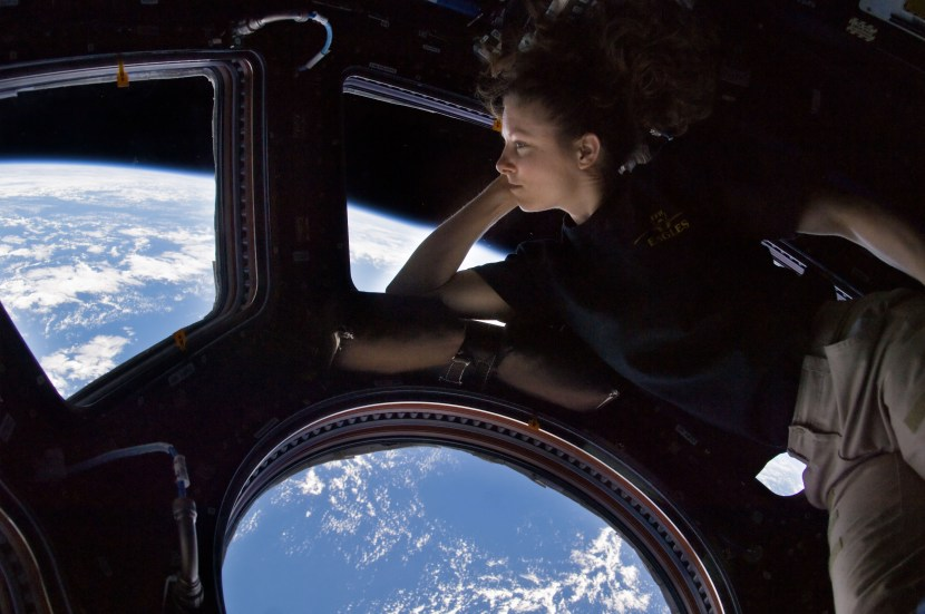 ISS024-E-014263 (11 Sept. 2010) --- NASA astronaut Tracy Caldwell Dyson, Expedition 24 flight engineer, looks through a window in the Cupola of the International Space Station. A blue and white part of Earth and the blackness of space are visible through the windows.