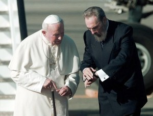 (FILES) This file photo taken on January 20, 1998 shows Cuban President Fidel Castro(R) looking at his watch as he and Pope John Paul II(L) walk on the tarmac of the Jose Marti international airport in Havana 21 January moments after the Pope arrived for a five-day four-city tour of the island-nation. After surviving more than 600 assassination attempts, defying 10 US presidents and shaping half a century of history, Fidel Castro celebrates his 90th birthday Saturday. / AFP PHOTO / MICHEL GANGNE / TO GO WITH AFP STORY