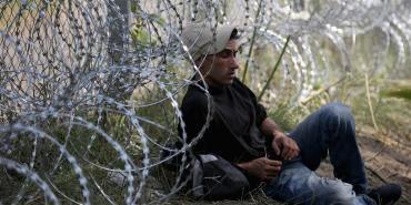 Un migrante appoggiato al muro che divide Ungheria e Serbia, 175 km di filo spinato.
