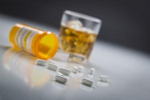 Several Prescription Drugs Spilled From Fallen Bottle Near Glass of Alcohol.