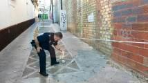Un agente de la Policía Local retira uno de los cascotes caídos/ José Luza Boza