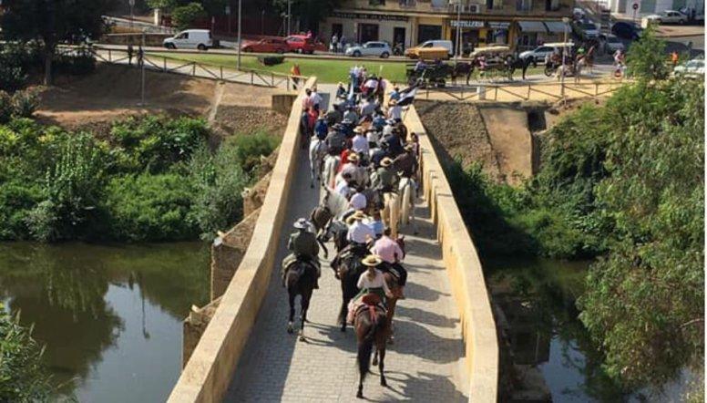 Los romeros cruzando la pasarela sobre el río Guadaíra / Hdad. San Mateo