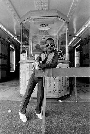 Dawoud Bey, A Boy in front of the Loew's 125th Street Movie Theater, 1976, printed by 1979. Photograph, gelatin silver print on paper. 20 7/8 x 18 7/8 x 1 1/4 in. © Dawoud Bey; Credit: Courtesy of the Broad