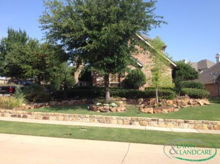 brick landscaping with raised bed tree plots and shrub garden in texas