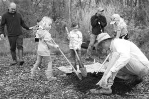 Girl Scout troop planting an apple tree at the Lawrence Community Orchard
