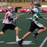 long pole dodging past midfielder youth high school lacrosse game