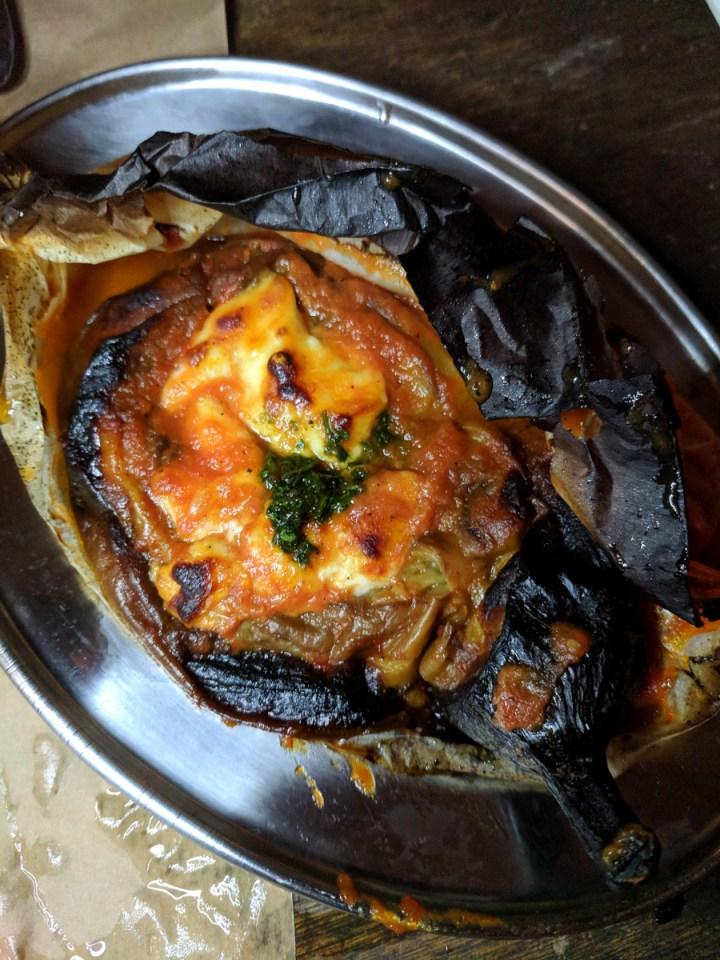 Berenjena entera asada con salsa de tomate y queso en Romano