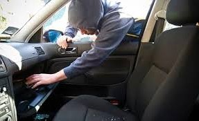 Photo of someone breaking into a car