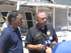 Nevada Governor Brian Sandoval and Lincoln County Sheriff Kerry Lee speak with the media in front of the home where two explosions occurred on July 13. Sandoval surveyed the damage and met with community members during a visit on July 15.