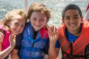 Image of three waving kids enjoying a boat trip to use the ROV