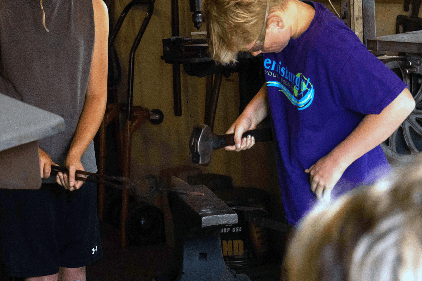 Boy hammering on an anvil