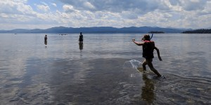Child runs through shallow water to waiting adults