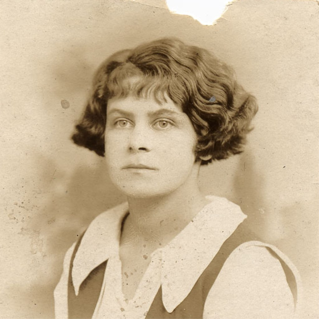 A sepia-colored photograph portrait of a white teenage girl circa 1918. Her dark wavy hair reaches her ears, she has a neutral expression on her face, and she wears a white collar top.