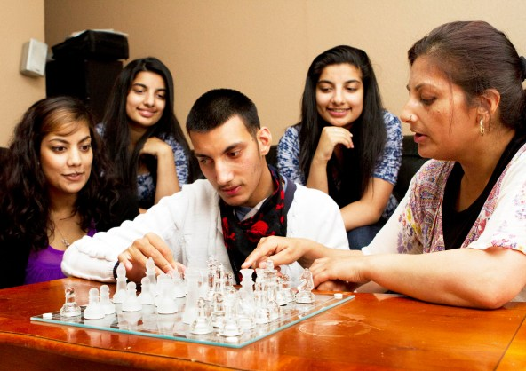 Image of a young person with additional support needs playing chess with friends and family