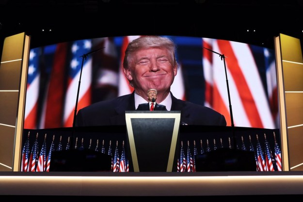 Trump at the RNC, standing and grinning ominously at a podium in front of a huge screen, zoomed in on his face, and a dizzying array of American flags.