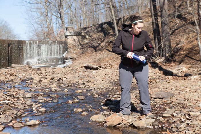 Female in front of waterfall and stream with reusable water bottle