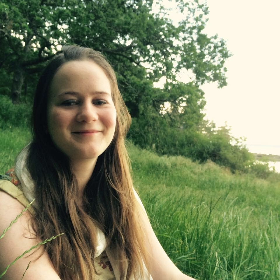 Jenna sits in a field of tall grass, smiling at the camera. Her light brown hair cascades over her shoulders. Lush green trees can be seen in the background.