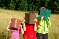 Children with face in books outdoors