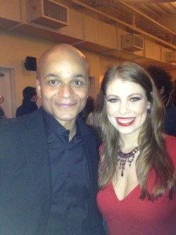 Leandra Ramm picture, wearing red dress with a bald gentleman in black suit middle close up Take One