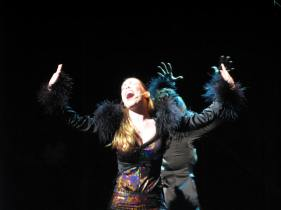Leandra Ramm picture, singing and wearing a furry and sparkling black dress Take One