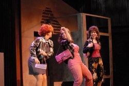 The Full Monty at The Media Theatre, Leandra wearing a wig, red shirt, and dark suit Take Three
