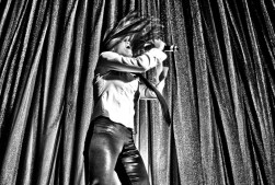 Leandra Ramm black & white picture, wearing white dress and dark pants standing and singing loud with a mic