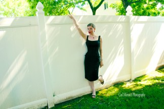 Leandra Ramm picture, wearing black dress leaning on a white fence Take Three