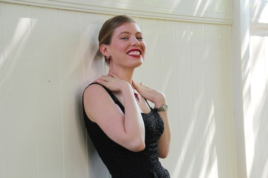 Leandra Ramm picture, wearing black dress leaning on a white fence Take One
