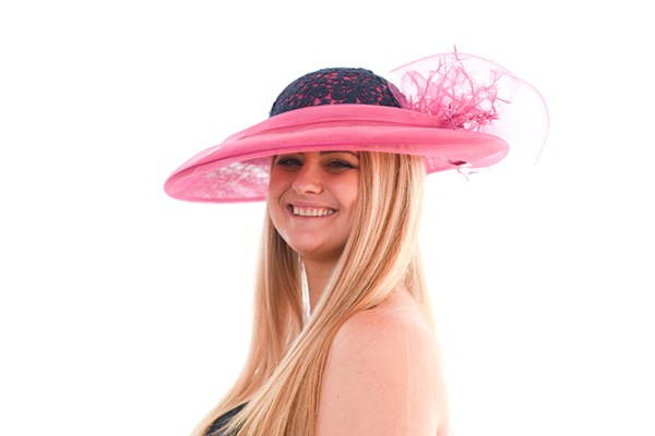 Raspberry Pink brimmed hat with navy lace crown tilted at an angle to the left of smiling models head, she looks directly to the camera
