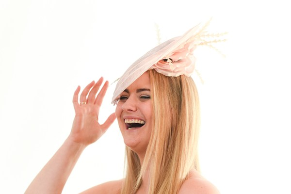 Light Pink Hatinator with underside silk flower visiabe on the laughing model as she raises her hand.