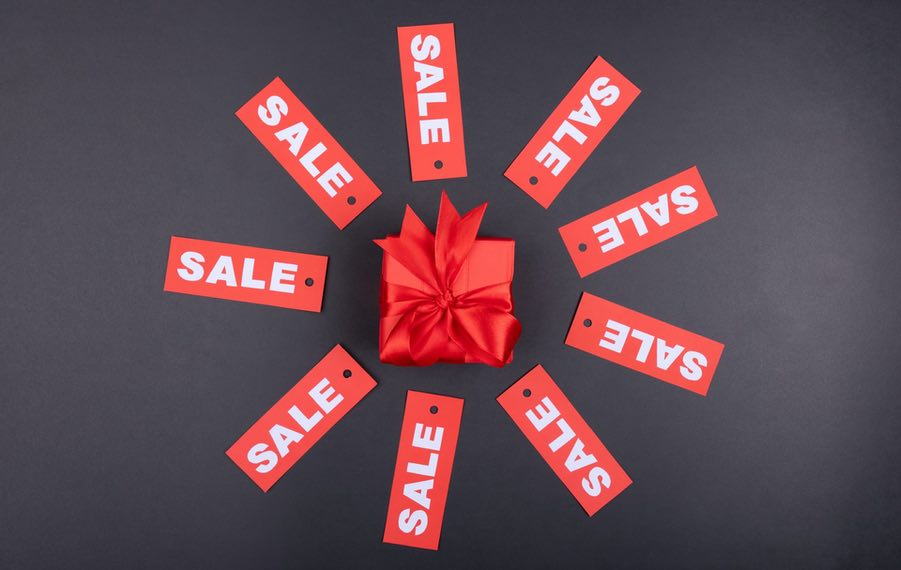 Sales signs in a circle around a red bow and box