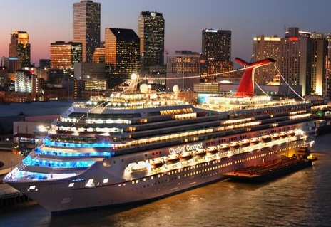 The Carnival Conquest, a new 110,000-gross-registered ton cruise ship owned by Miami-based Carnival Cruise Lines is aglow with light against the New Orleans skyline Tuesday, Nov. 12, 2002, as it receives fuel from a barge. The ship can carry 3,700 guests and offers seven-day western Caribbean cruises.(Photo by Andy Newman/CCL)