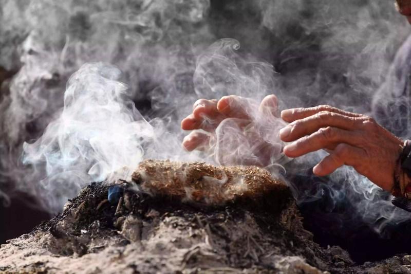 Image recadrée de la main sur la fumée qui émet de l'encens au temple