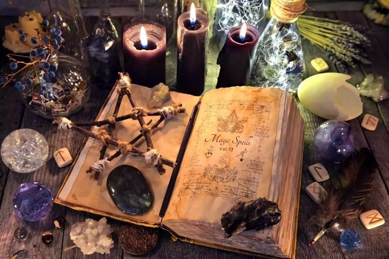 Vieux livre de sorcière avec pentagramme, bougies noires, cristaux et objets rituels