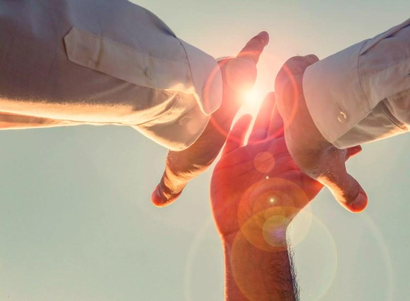 Mâinile decupate dând cinci în fața cerului