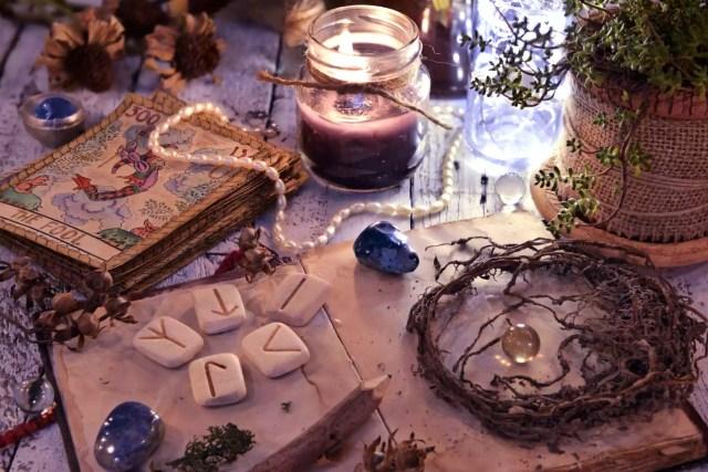 Vechile cărți de tarot punte, rune și rădăcini uscate cu carte pe masă